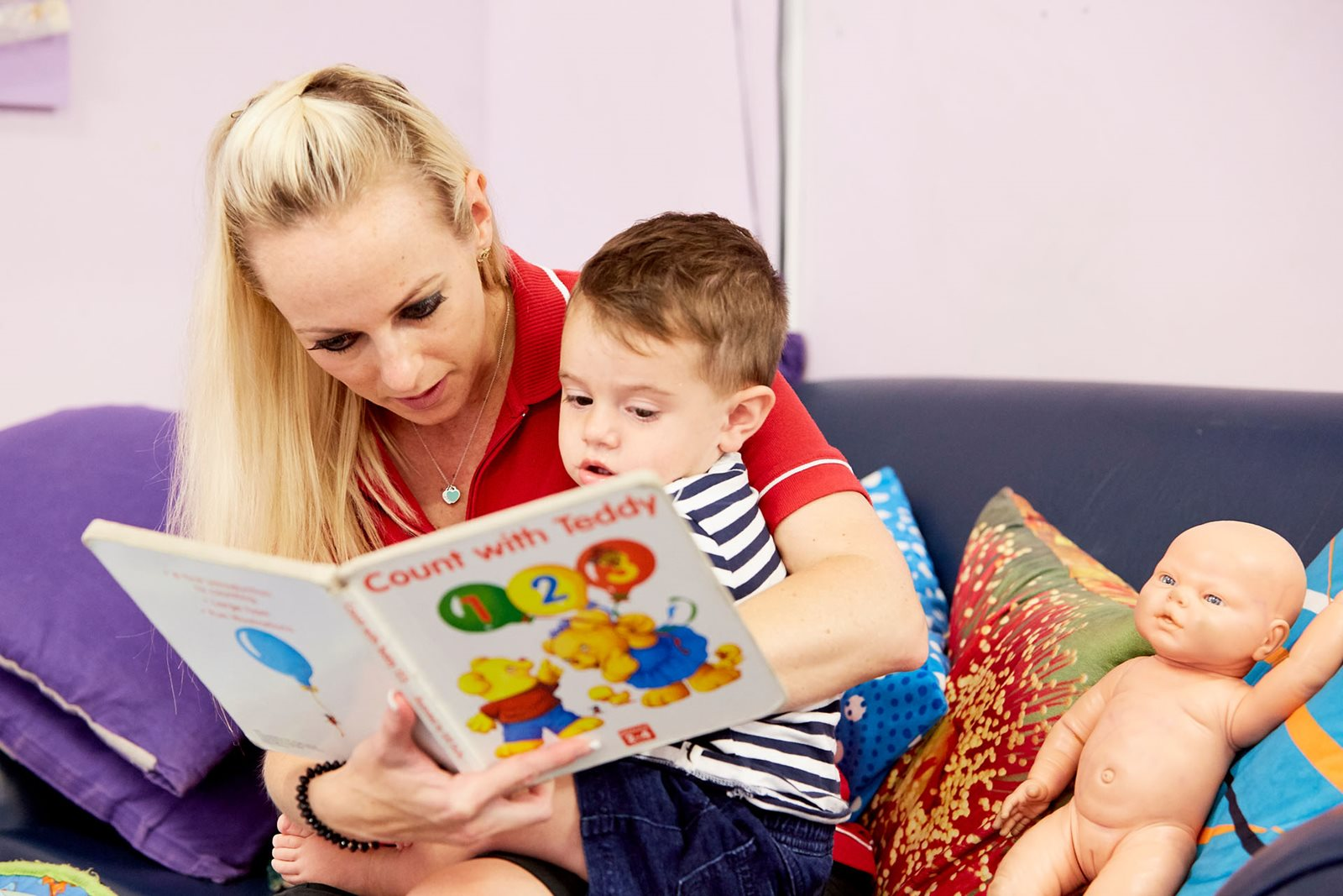 Child care educator reading to child in classroom