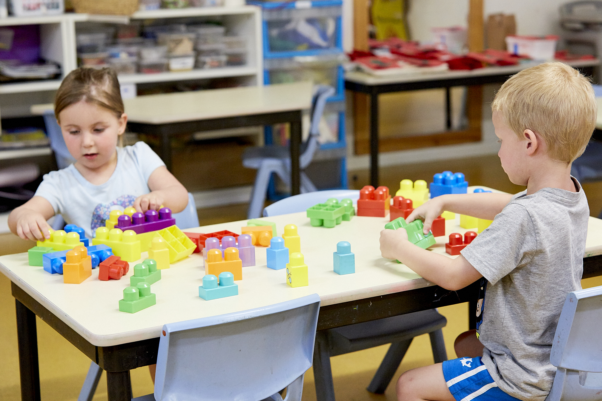 Children playing with building blocks on table in child care classroom